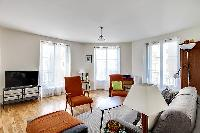 minimalist living room with a grey sofa bed, two apricot armchairs, a center table, and a cabinet wi