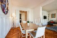 chic dining set for six with accessto the living area and kitchen in a 2-bedroom paris luxury apartm
