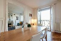 chic dining set for six with French window and access to the living area in a 2-bedroom paris luxury