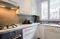 A compact kitchen in a 2-bedroom paris luxury apartment