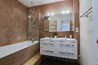 bathroom fully-equipped with double sinks, a bathroom cabinet, a mirror, and a bathtub with a detach
