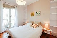 chic master bedroom is furnished with a queen-size bed, two bedside tables, built-in shelves, and Fr