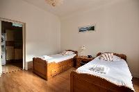 second bedroom is equipped with two single beds, a wardrobe, and a chest of drawers in a 2-bedroom P