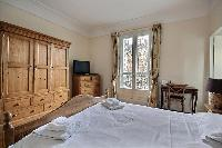 first bedroom with an en-suite bathroom furnished with double sinks, a bathroom cabinet, mirrors, an