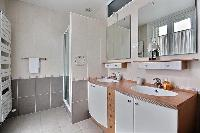 an en-suite bathroom with a sink, a bathroom cabinet, a mirror, and a shower area in a 2-bedroom Par