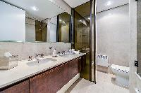 en-suite bathroom fully-furnished with a sink, a bathtub, a bathroom cabinet, a toilet, and bidet
