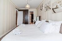 third bedroom furnished with a dresser, a queen-size bed, French windows with access to the terrace