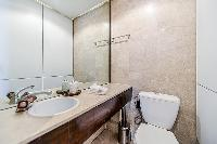 en-suite bathroom with double sinks, a bathtub, a toilet, and bidet