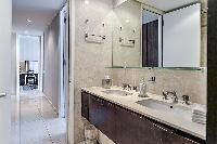 bathroom equipped with double sinks, a toilet, and a shower area in a 4-bedroom paris luxury apartme