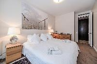 fourth bedroom furnished with a queen-size bed, two bedside tables with lamps, a nightstand, and Fre