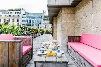 terrace with pieces of patio furniture in a 4-bedroom paris luxury apartment