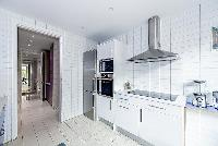 spacious blue and white kitchen situated near the terrace