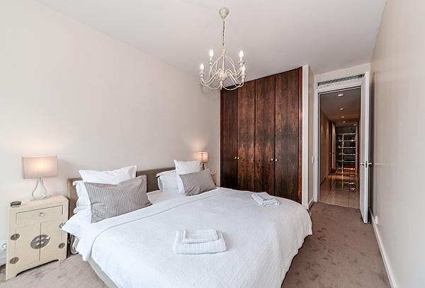 first bedroom furnished with a queen-size bed, two bedside tables, a wardrobe, and French windows in