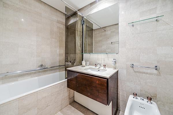 en-suite bathroom fully-furnished with a sink, a bathtub, a bathroom cabinet, a toilet, and bidet