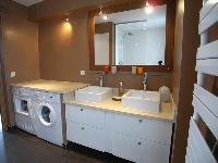 bathroom  with double sinks, a washing machine and clothes dryer, and an iron and ironing board in a
