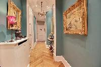 hallway hanged with classic wall of arts in paris luxury apartment with access to the bedrooms