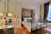 classic bedroom equipped with a queen-size bed, a large wardrobe, built-in cabinets, and a nightstan