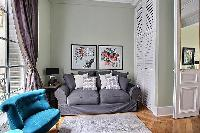 comfortable grey sofa and turquiose seat in Paris luxury apartment