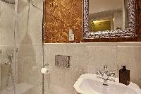 en-suite bathroom fully-furnished with double sinks, a bathroom cabinet, a toilet, and a shower area
