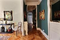 hallway hanged with classic wall of arts in paris luxury apartment