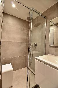 bathroom with a sink, bathroom shelves, a vanity mirror with lights, and shower area with a rainfall