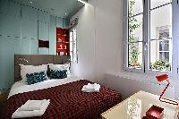 first bedroom with a queen-size bed, wall shelves, and a desk with a lamp in a 2-bedroom Paris luxur