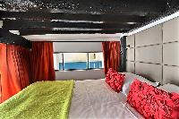 second bedroom with a queen-size bed, and a bedside table with a mirror in a 2-bedroom Paris luxury