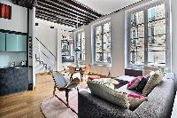 comfortable living area with an L-shaped sofa, a center table, and chairs in a 2-bedroom Paris luxur
