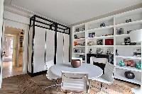 round table with 4 white chairs, shelves, and ornamental fireplace in a Paris luxury apartment