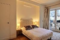 chic bedroom with a queen-size bed, built-in cabinets, bedside tables, lamps, drape curtain and tall