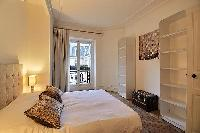 chic bedroom with a queen-size bed, shelves, chest, bedside tables, lamps, drape curtain and tall wi
