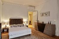 bedroom two with queen size bed, bdside tables, lamps, and ornamnetal fireplace in a Paris luxury ap