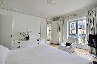 white bedroom three with queen size bed, armchair, TV and cabinet drawers in a Paris luxury apartmen