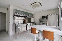 cozy kitchen with white breakfast bar and stools in Paris luxury apartment