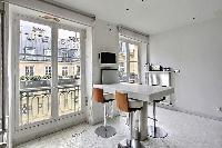 white breakfast bar and stools, TV, and tall windows in Paris luxury apartment