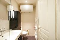 well-designed bathroom with shower, sink and toilet in a 1-bedroom Paris luxury apartment