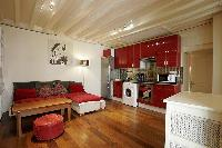 warm living area and space efficient kitchen in a 1-bedroom Paris luxury apartment