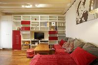 warm living area with TV, shelves, wooden center table, and an L-shaped sofa in a 1-bedroom Paris lu