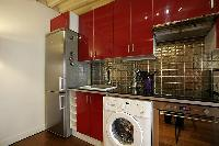 open kitchen in red hue with washer and dryer in a 1-bedroom Paris luxury apartment