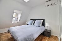 second bedroom with a queen-size bed, two bedside tables with lamps, and a built-in closet with a mi