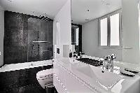 sleek black and white bathroom fully-equipped with a toilet, double sinks, a bathroom cabinet, a mir