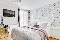 chic bedroom with a queen-size bed, built-in shelves, side tables, and a television in a 2-bedroom p