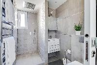 cozy bathroom in slate grey with a toilet, a sink, bathroom drawers, a mirror, a shower area with a