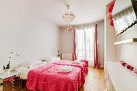 chic bedroom with two single beds joined together to form a queen-size bed, shelves, a study corner,