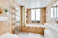 cozy bathroom in brown and white motif with a toilet, double sinks, bathroom shelves, a mirror, a ba