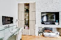 living area with bookshelves, a TV, and a desktop in a 2-bedroom paris luxury apartment