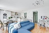 spacious living space with an L-shaped muted blue sofa, built-in shelves with decorative pieces, a t