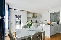 open plan kitchen and dining area with a four-seater dining table in a 2-bedroom paris luxury apartm