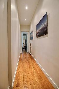hallway with wooden floors and paintings in a 3-bedroom Paris luxury apartment