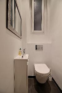 a water closet with a toilet and a sink in a 3-bedroom Paris luxury apartment